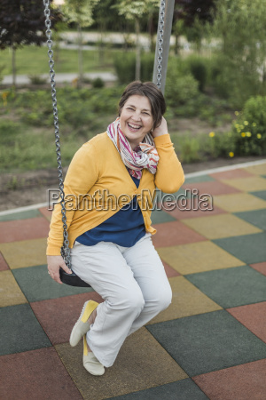 happy senior woman enjoying on swing