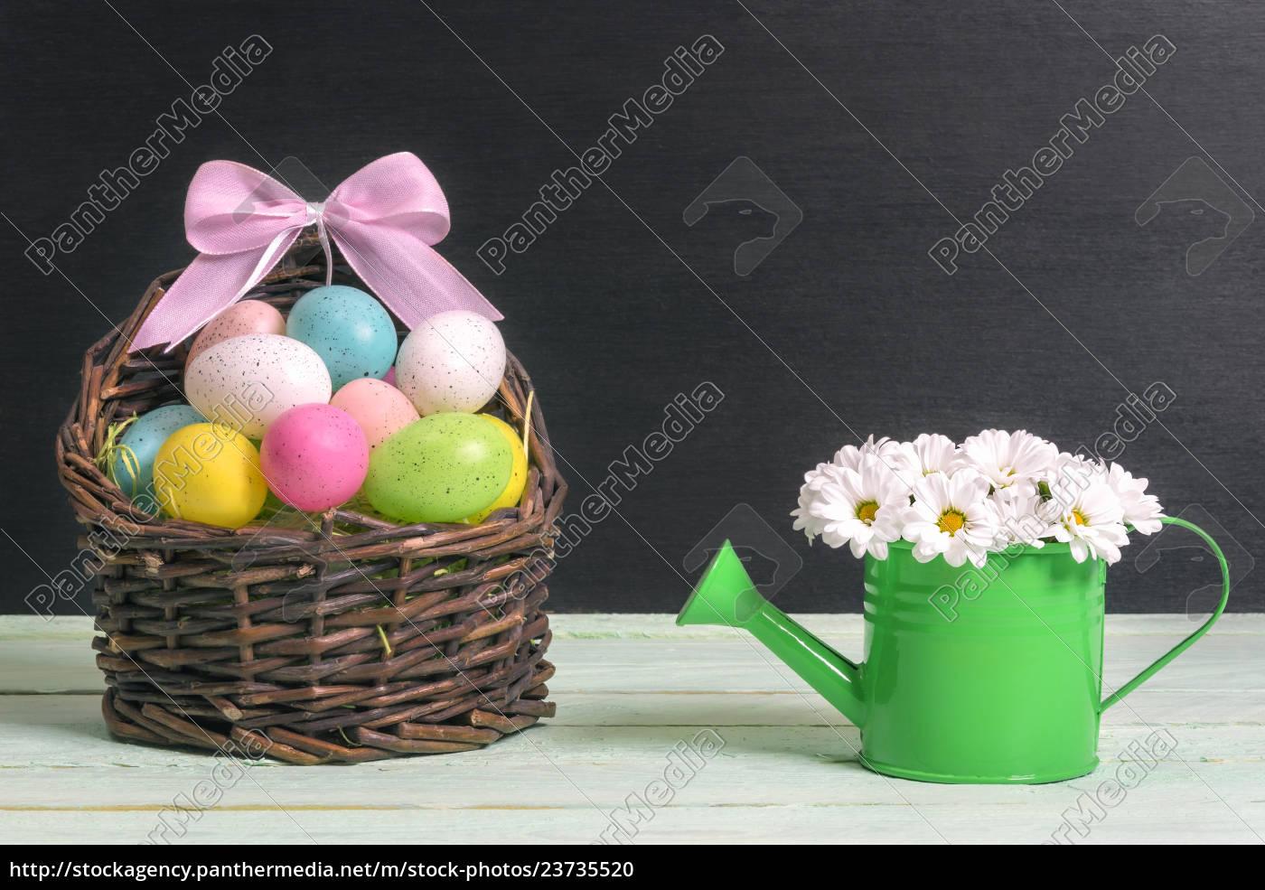 korb, mit, ostereiern, und, einem, gänseblümchenblumenstrauß - 23735520