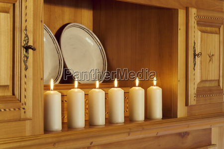 burning white candles on a cabinet