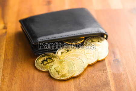 golden bitcoins in leather wallet