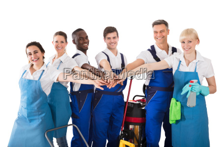 group of happy janitors stacking hands