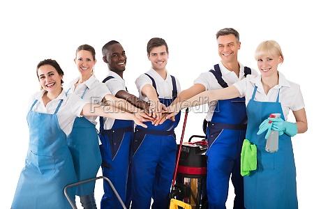 gruppe der gluecklichen janitoren stapeln haende