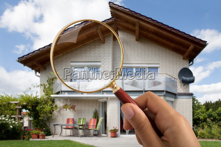 persons hand holding magnifying glass over