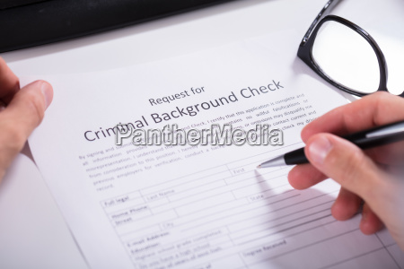 person hand filling criminal background check