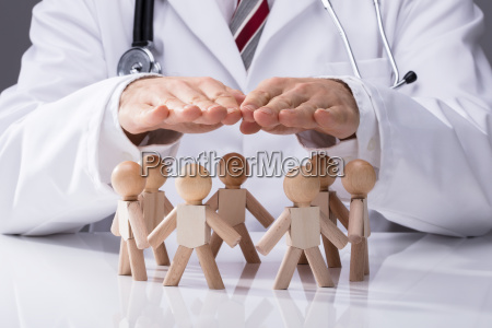 doctor protecting wooden figures