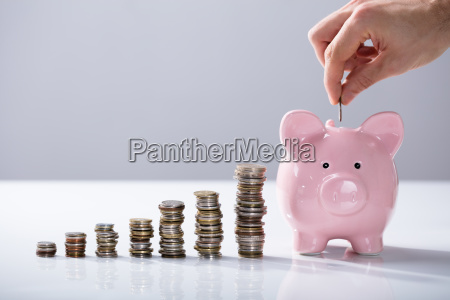 person inserting coin in the piggybank