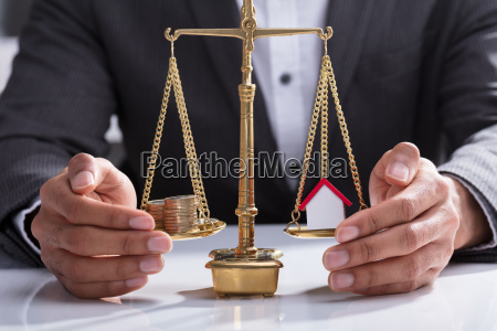 businessperson protecting stacked coins and house