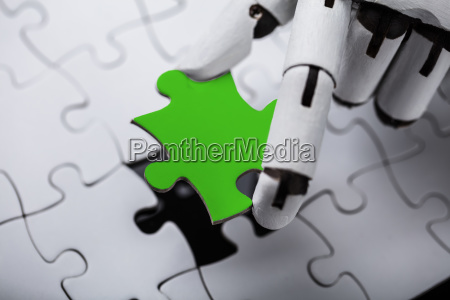 robot holding green jigsaw puzzle