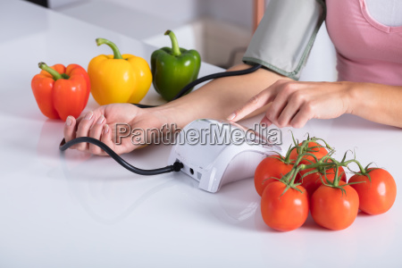 woman checking blood pressure on table