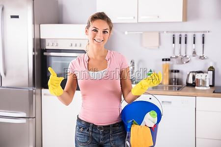 glueckliche frau welche die gelben handschuhe