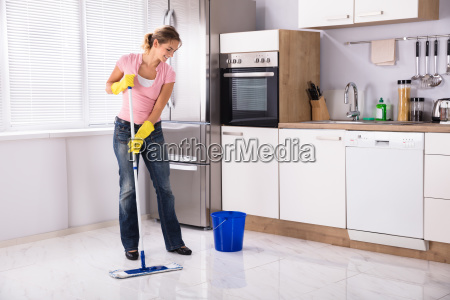young woman cleaning kitchen floor with