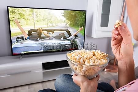 die, hand, der, person, die, popcorn, hält, während - 23776272