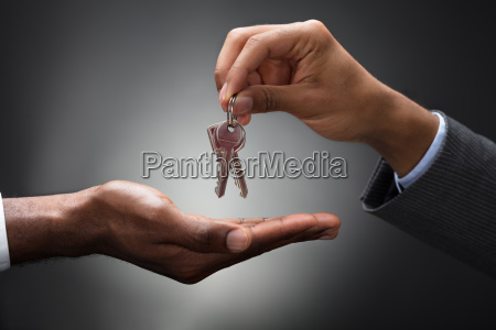 hand passing keys to new owner