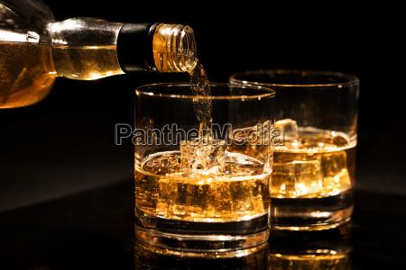 versare whisky in un bicchiere di