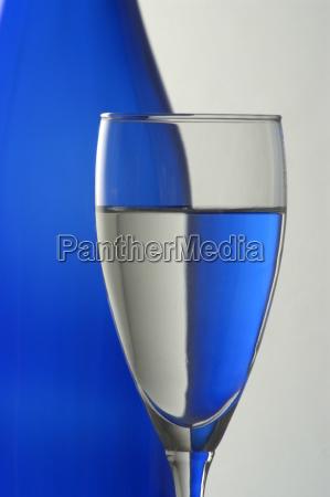 blaue flasche und sektglas teilansicht