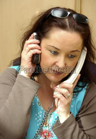 frau mit zwei telefonen am ohr