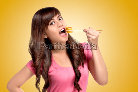 young asian woman eating sushie with