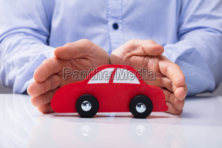 person protecting red car