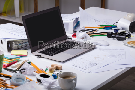 open laptop on the messy desk