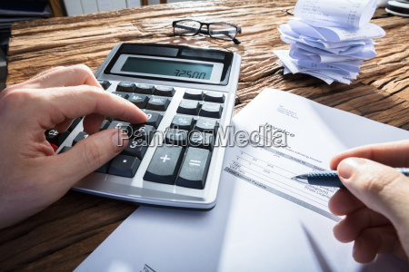 persons hand calculating invoice