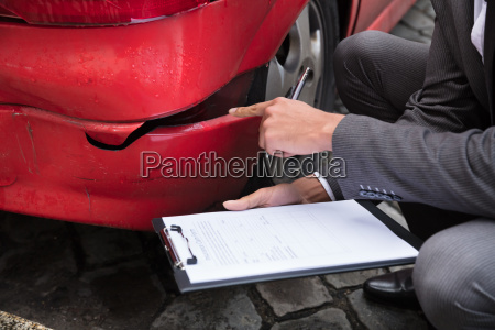 insurance agent writing on clipboard after