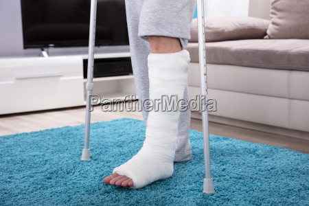 man with broken leg walking on