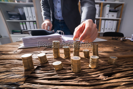 businessperson calculating stacked coins