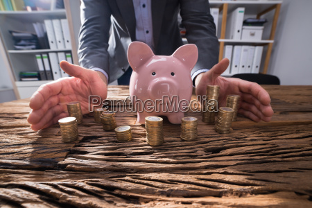 businesspersons hand protecting stacked coins and