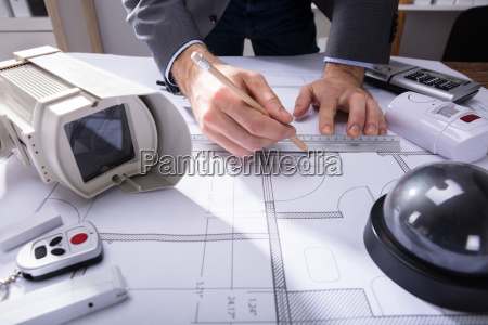 architect drawing plan on blueprint