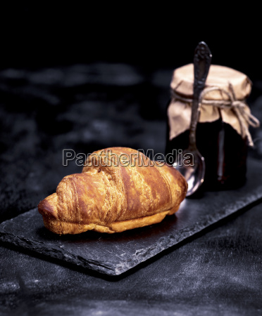 baked croissant and a jar of