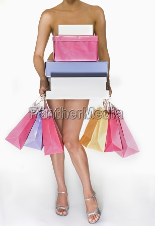 nude female holding shopping bags and