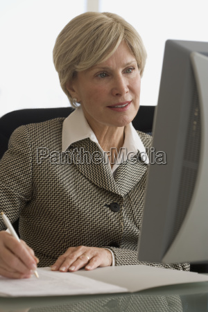senior businesswoman looking at computer and