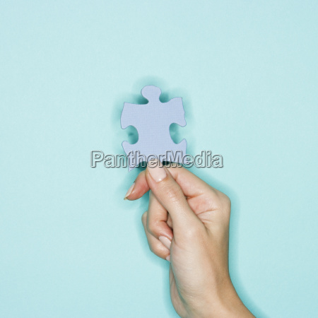woman holding jigsaw puzzle piece