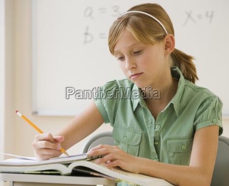 teenaged, mädchen, das, am, schuleschreibtisch, schreibt - 23889440