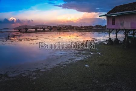sunset over small fishing village sape
