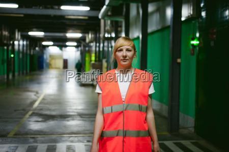 mitarbeiterin in orangefarbener robeweste im arbeitsraum