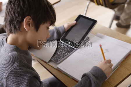 schoolboy 12 13 with digital tablet