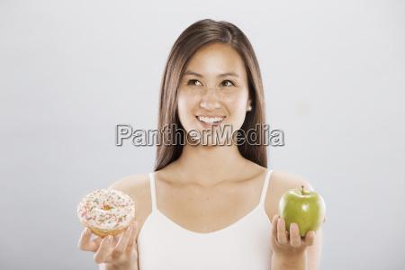 woman holding an doughnut and an