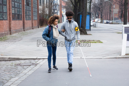 woman helping blind man while crossing