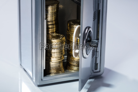 open safe with stacked coins