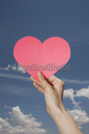 womans hand holding pink heart shape