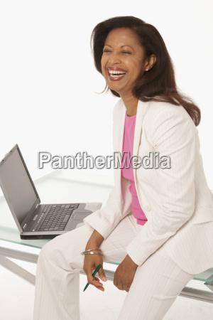 happy businesswoman sitting on desk