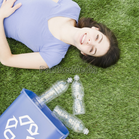woman lying on grass beside recycling