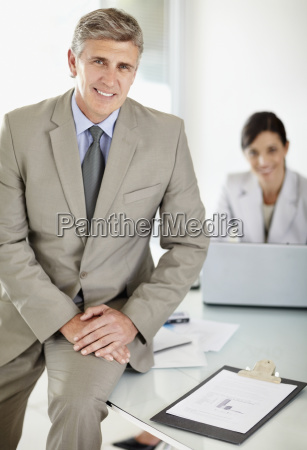 mature business sitting on desk with