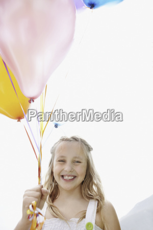 young girl holding balloons