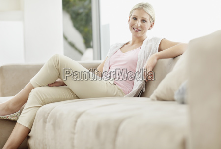 pretty blond woman sitting on couch