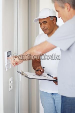mann der alarmsystem ueberprueft