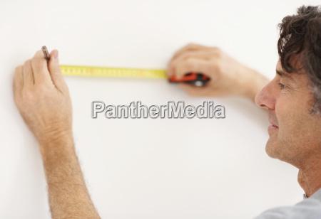 carpenter measuring wall