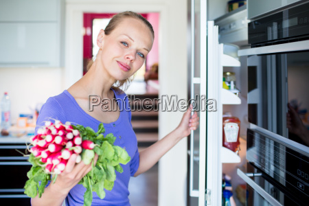 pretty young woman taking fresh vegetables