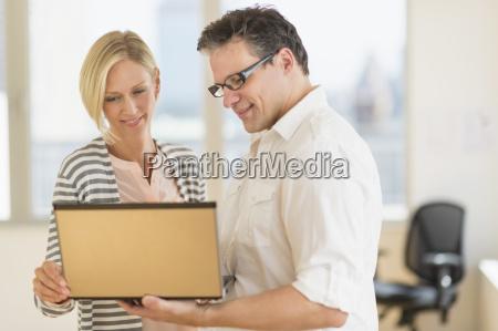 geschaeftsmann und frau die laptop halten